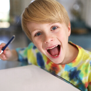 A very happy young boy drawing with a pen
